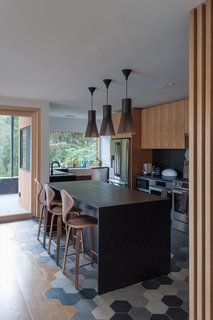 """The kitchen was opened up to make way for more counter space and a large island. All appliances were updated with Bosch products. """"The client was interested in a simple material and color palette of white oak uppers, matte black lowers with Corian countertops, and white gyp walls accentuated by patterned tiles,"""" the architects say. The pendant lights are by Secto design and the bar stools by Cherner."""