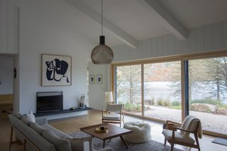 The minimalist fireplace was painted over and reduced in size, then articulated with cantilevered cleft slate hearths on either side. Seating is from the Design Within Reach Raleigh collection.