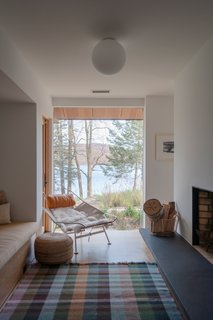 Behind the double-sided fireplace is an intimate reading room alcove with a stellar view of Candlewood Lake. The chair is a vintage Flag Halyard chair.