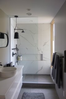 The guest bathroom boasts a minimalist look achieved with large, cement floor tiles and Statuario-style tiles on the walls.