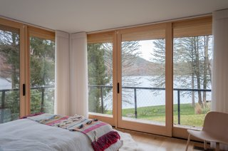The largest guest bedroom is surrounded by walls of glass framing views of Candlewood Lake.