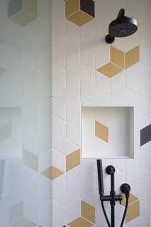The kids' bathroom and entry bathroom sport colorful, geometric tile for a playful touch.