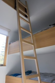 A ladder leads to the high-lofted bunk bed.