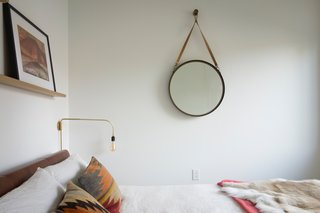 A look inside the third bedroom, located on the west side of the north wing. The hanging mirror is from CB2. All bedding is from Design Within Reach and CB2.