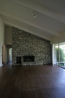 """Before: The double-sided fireplace in the original living room was """"visually noisy"""" and detracted from outdoor views."""
