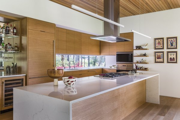 A waterfall-edge quartz-topped island creates a dramatic statement in the minimalist kitchen. A window cutout behind the sink overlooks forest views to the west.