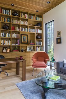 The cozy study is furnished with custom timber shelving, a Gus Modern Jane sectional, a Womb chair, an ottoman designed by Eero Saarinen for Knoll, and a Noguchi table.