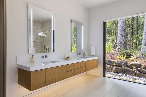 Mosa porcelain tile lines the bathroom floors. Pictured here is the ground-floor master bath, with massive walls of glass framing forest views.