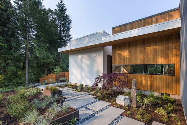 A view of the outdoor walkway that connects the patio to the master bedroom. The exterior is clad in traditional stucco and tongue-and-groove vertical cedar siding.