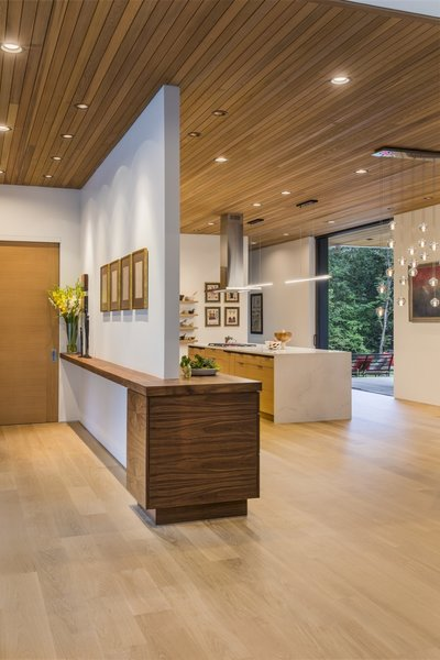 The entry leads directly to the open-plan kitchen, dining area, and living room, where full-height sliding doors extend the living spaces to the outdoors.