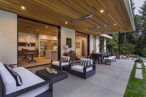 Indoor/outdoor living is emphasized throughout the design. Pictured is the protected terrace with Restoration Hardware seating, a Marbella Metal Rectangular table, and acid-washed concrete flooring.