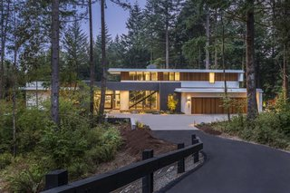 """A true """"forested retreat,"""" the home is accessed via a private entry road through the woods."""
