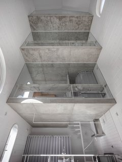 """The section and internal void works as a space where light travels around and produces a very calm sense of interiority. But also, from the rooms, it becomes a sort of interior courtyard,"" Zamarbide said. The unfinished concrete slabs contrast with the cement block walls painted white."