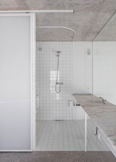 10cm x 10cm white tiles line all the bathroom walls and floors. The same tiles pop up in the kitchen.