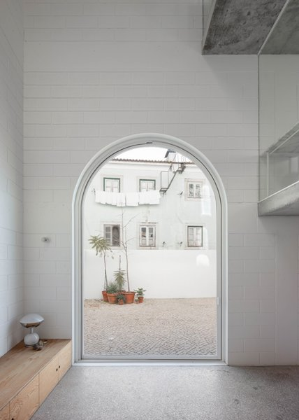 Fitted with glass, a massive arched pivot door, made by Much More than a Window, provides access to the outdoor patio.