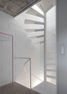 At the rear of the house is a minimalist spiral staircase that winds up all four floors.