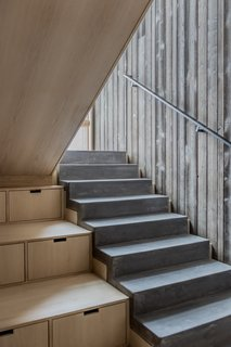 Poured concrete stairs step down alongside built-in storage.