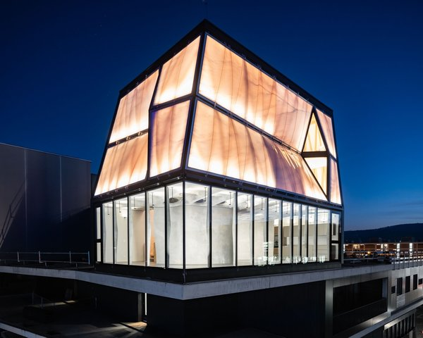 A lighthouse of cutting-edge digital fabrication, the building glows like a beacon at night.