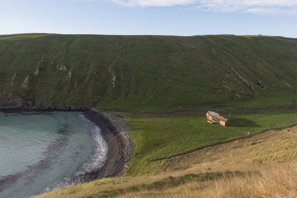 Nestled on a crescent-shaped surf beach on South Island's Banks Peninsula sits a deceptively simple beach house. Scrubby Bay is a rustic retreat flush with modern luxuries and breathtaking scenery at every turn.