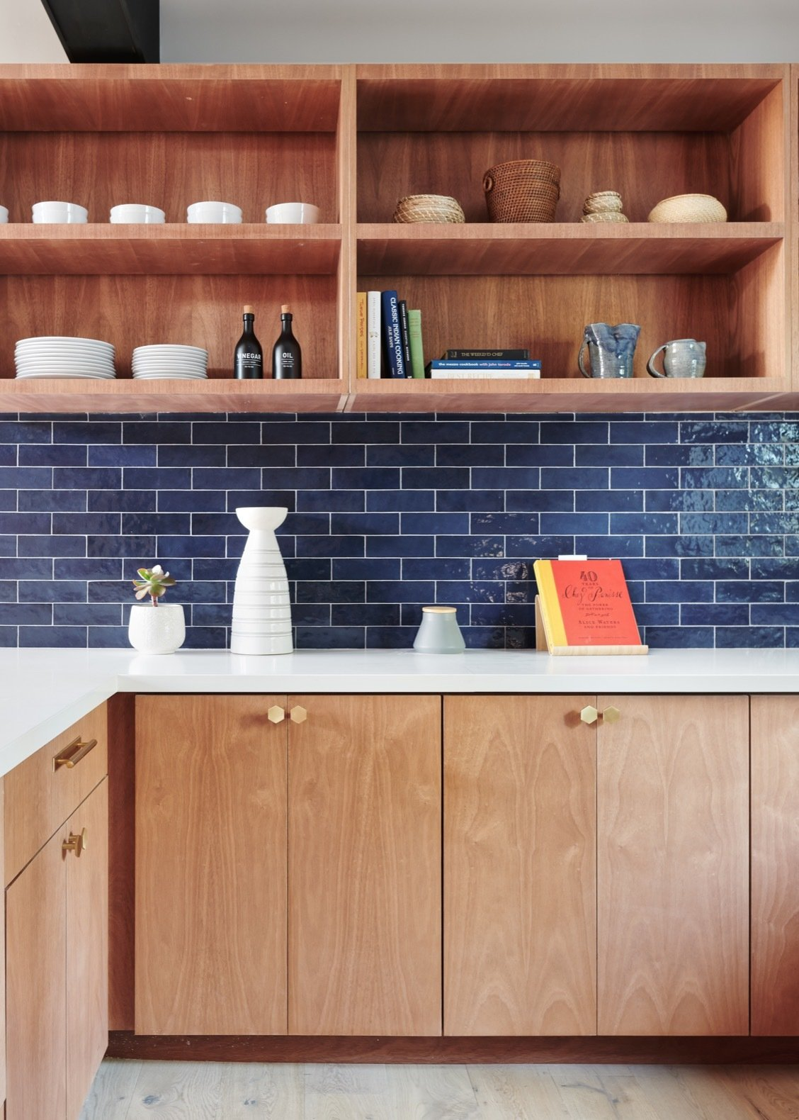The updated kitchen features an Elite Tile backsplash, white quartz countertops, and new plumbing and lighting.  Photo 16 of 25 in Before & After: A Midcentury Wrapped Around an Oak Tree Turns Over a New Leaf
