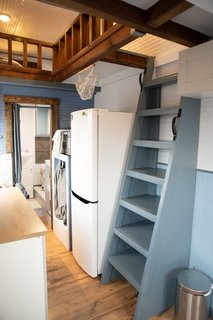 A bookcase ladder provides access to the double loft space above.
