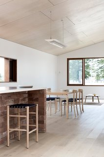 Tongue-and-groove Piccolo Eterno oak floorboards line the home. The dining room includes a vintage Alvar Aalto table paired with Lightwood Chairs by Jasper Morrison.