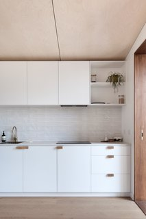 In the 236-square-foot studio is a kitchen dressed in a minimalist palette.