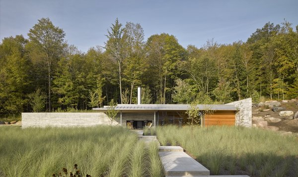 Cedar, glass, and concrete combine in this minimalist pool house that draws inspiration from Mies van der Rohe's 1929 Barcelona Pavilion. The pool house, built into a mountainside west of Montreal and designed by Halifax–based MacKay-Lyons Sweetapple Architects, employs board-formed concrete for the home's expressive exterior.