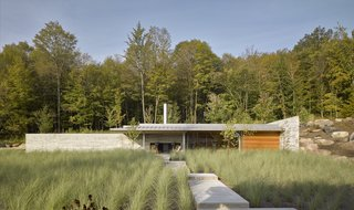 A zigzagging path built of locally sourced Stanstead granite leads throughs a field of grasses to the Pool House.
