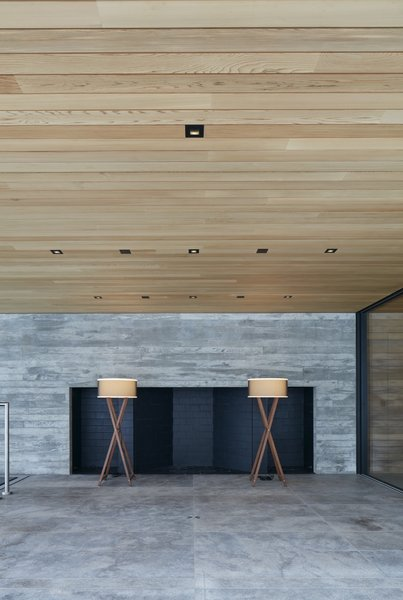 The outdoor wood-burning fireplace is placed inside the board-formed concrete wall. The floors are locally quarried Stanstead granite.