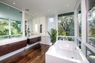 The master bath includes double vanities, a freestanding bathtub, and a hidden built-in television.