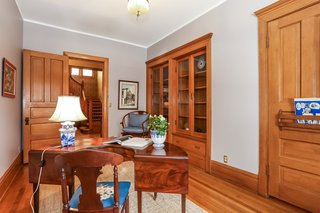 The den is accessible from the foyer and the family room and comes with built-in bookcases with glass doors and drawers.