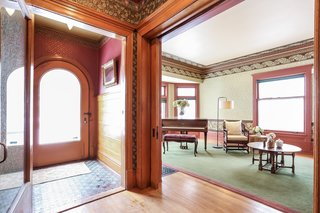 Fitted with original flooring and paneling, the light-filled vestibule includes a large curved door with beveled glass and a large swinging door that leads to the foyer.