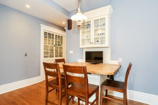The remodeled breakfast room comes with a built-in table with a display cabinet and six chairs. The built-in hutch in the corner is original to the home. The renovation converted the antique kerosene fixture to run on electricity.