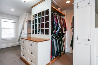 The master walk-in closet includes custom cabinets and a washer/dryer with a folding surface.