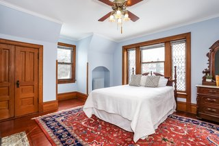 The beautiful second bedroom in the southwest corner of the home has an original fireplace and windows with leaded glass panels.