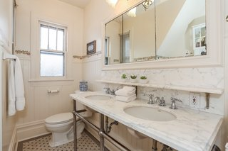 The second-floor hallway bath features reproduction tile flooring, a vintage-style large mirror, and a double marble-top vanity.