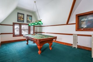 Formerly the ball room, this expansive third-floor space now serves as a carpeted game room. The pool table and an L-shaped LazyBoy couch are included.