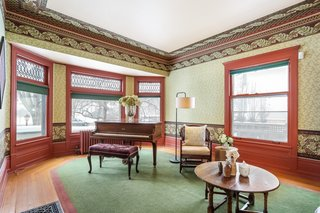 The living room overlooks the street with a large bay window with original leaded glass panes. The original hardwood floors include an exterior oak border and an inner area of pine (covered by the rug, which comes with the home).