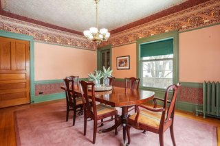 The dining room includes a built-in hutch with glass display doors and a lower cabinet, as well as a period light fixture.