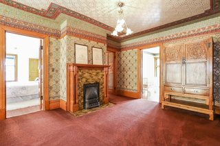 The second-floor landing is lined with carpet and comes with an original fireplace with tile surround and a wooden mantel.