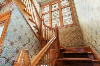 An original stained glass nine-panel window illuminates the stairway to the second floor. All wallpaper was created specifically for this home using architectural renderings for the design, and then hung by a Bradbury-licensed wallpaper artisan.