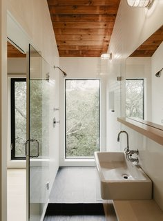 The guest bathroom features a full-height window with immersive canopy views.
