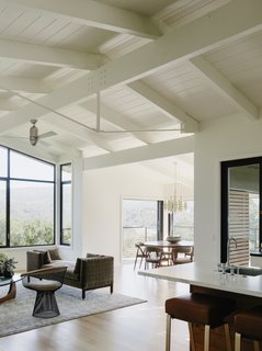 The architects preserved the existing beamed ceilings, which give the open-plan living area an airy feel. The living area is dressed with a vintage <i>tête-à-tête</i> sofa by Edward Wormley, a Warren Platner chair, and an Isamu Noguchi table.