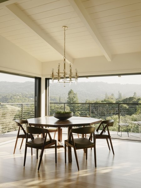 Surrounded by retractable glass doors, the dining area opens up to the landscape. A custom Gianni Corvasce Restoration walnut table is combined with vintage Kai Kristiansen dining chairs and a 1970s brass-and-Lucite chandelier.