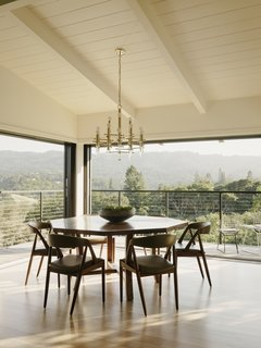 Surrounded by retractable glass doors, the dining area opens up to the landscape.