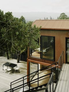 The water-resistant ipe wood deck wraps around two existing trees.