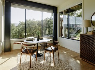 Beneath the dining area is a small sitting room flooded with light from three sides through bronze anodized windows with automatic translucent shades by Fleetwood Windows & Doors.