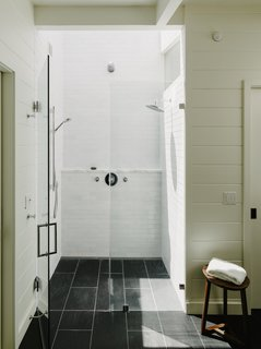 White ceramic Fireclay tile wraps around the shower. Skylights bathe the master bath in natural light.