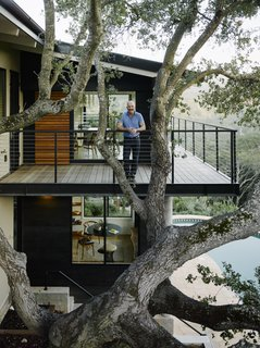 Malcolm Davis stands behind the specimen oak tree on the new cantilevered wraparound deck.